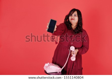 Attractive south asian woman in deep red gown dress posed at studio on pink background and use old vintage telephone with modern mobile phone.