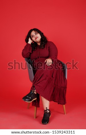 Attractive south asian woman in deep red gown dress posed at studio on pink background sitting on chair.
