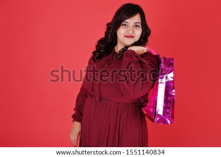 Attractive south asian woman in deep red gown dress posed at studio on pink background with bright colored shopping bags.