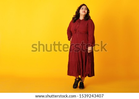 Attractive south asian woman in deep red gown dress posed at studio on yellow background.