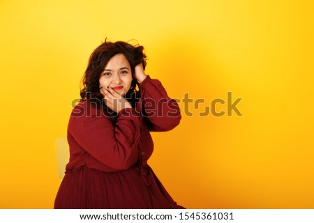 Attractive south asian woman in deep red gown dress posed at studio on yellow background and sitting on chair.