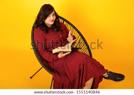 Attractive south asian woman in deep red gown dress posed at studio on yellow background sitting on chair with book.