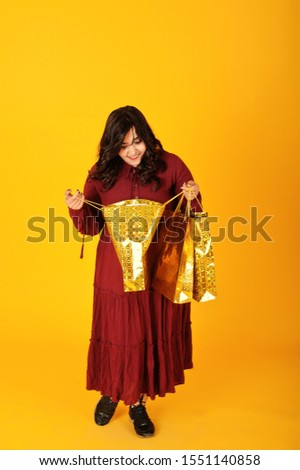 Attractive south asian woman in deep red gown dress posed at studio on yellow background with golden shopping bags.
