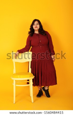 Attractive south asian woman in deep red gown dress posed at studio on yellow background with chair.