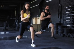 Attractive sport couple doing fitness at gym.