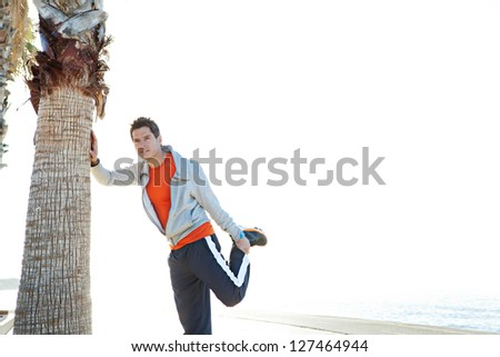 Attractive sports man stretching his legs while leaning on palm tree trunk by the sea in an open sky space.