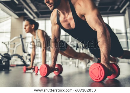 Stock Photo Attractive sports people are working out with dumbbells in gym