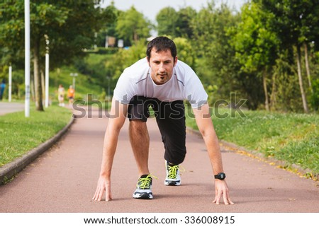 Attractive sportsman ready to sprint in a sports area outdoors Stock photo ©