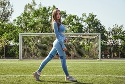 Attractive sportswoman posing outside at football field. Young woman model in stylish sport clothing smiling.