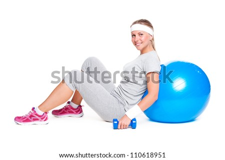 attractive sportswoman sitting with ball and dumbbells. isolated on white background