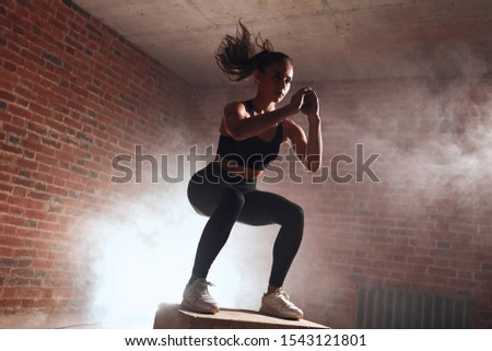 Attractive sporty female with long hair doing squats on wooden box. Process of jumping. Brickwall background