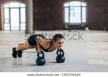 attractive sporty girl doing push ups with kettlebell.hobby, lifestyle, spare time, free time. copy space