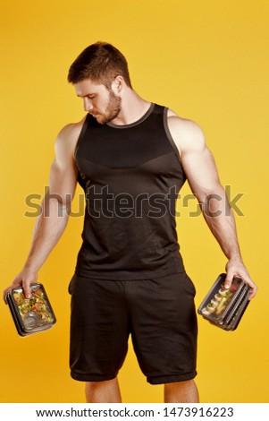 Attractive sporty man dressed in a black tank top and shorts, posing in studio on a yellow background with boxes of food. Healthy nutrition, daily diet
