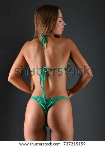 Attractive sporty woman in bikini posing on grey background.