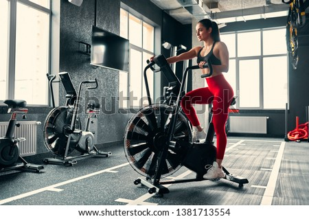 Attractive sporty woman in gym. Young perfect shaped brunette  training on bicycle