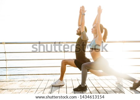 Attractive sporty young fitness couple wearing sportswear working out outdoors at the beach, stretching muscles