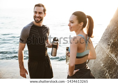 Attractive sporty young fitness couple wearing sportswear working out outdoors at the beach, having break, talking, drinking water