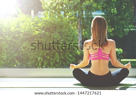 Attractive sporty young yogi woman wearing sportswear practicing yoga, sitting in padmasana lotus pose, meditating in spacious room w/ full length windows, green garden view. Background, copy space.