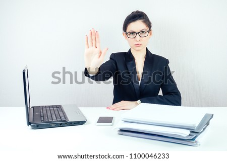 attractive strict brunette woman (business lady) in stylish business suit and glasses shows a hand gesture stop with laptop and a bunch of folders in the workplace office #1100046233
