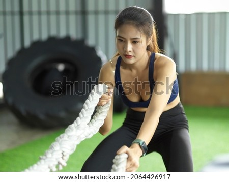 Attractive strong asian fitness woman doing battle ropes exercise at gym. weight training exercise session.