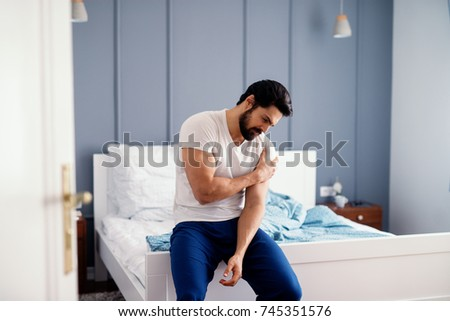 Attractive strong man sitting on the bed and holding painful shoulder with another hand. #745351576