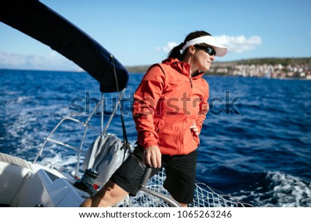 Attractive strong woman sailing with her boat #1065263246
