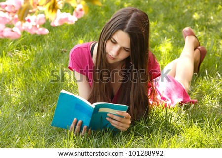Attractive student teen girl reading book on green spring grass
