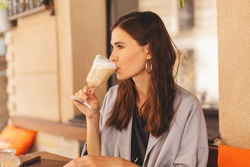 Attractive stylish beautiful woman sitting in city cafe in street, drinking coffee latte. Happy white woman with gorgeous hairstyle sitting on restaurant. Outdoor portrait of glad young lady in suit.