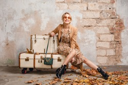 attractive stylish blonde woman in beige coat sitting on suitcases against wall in street, autumn fashion trend, wearing dress, boots, handbag, sunglasses, leaves on the ground, urban style