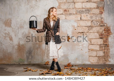 attractive stylish blonde woman in checkered jacket coat walking against wall in street in autumn fashion trend, wearing white lace dress, boots, handbag, leaves on the ground, urban style