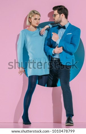 Stock Photo attractive stylish couple stepping through aperture on pink