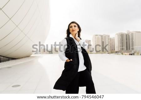 attractive stylish girl in a black suit walks around the city of Baku in Azerbaijan