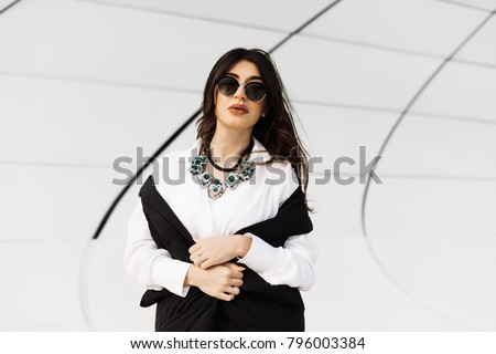 attractive stylish girl in black sunglasses walks around the city of Baku