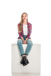 attractive stylish girl in checkered shirt and jeans sitting and looking at camera isolated on white