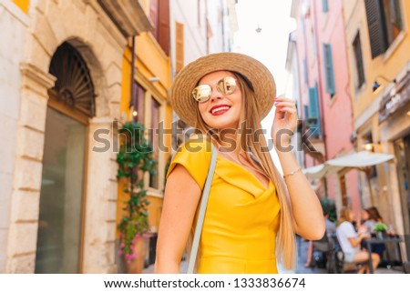Attractive stylish girl in stylish sunglasses and boater on the street of the city