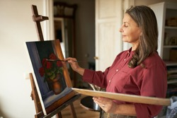 Attractive stylish mature retired female having inspired look holding brush and palette painting flowers on canvas using oil paint, standing in front of easel during art class for beginners