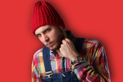 Attractive stylish model dressed in a lumberjack shirt, dungarees and a red cap. He is angry and isolated on red background.