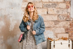 attractive stylish smiling blonde woman in jeans oversize jacket walking against wall in street, spring fashion trend, wearing dress, pink purse, black beret, urban style trend