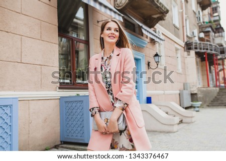 attractive stylish smiling woman walking city street in pink coat spring fashion trend holding purse, listening to music on earphones
