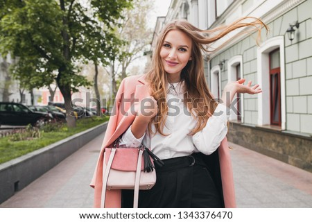 attractive stylish smiling woman walking city street in pink coat spring fashion trend holding purse, elegant style, waving long hair