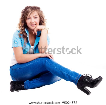 attractive stylish twenty year old woman wearing jeans and a blue jacket, isolated against white background