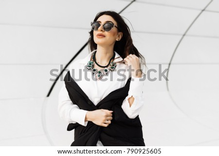 attractive stylish woman in a black suit and sunglasses walking around the city of Baku