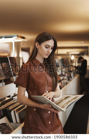 Attractive stylish young caucasian woman in brown dress, reading magazine, turn pages in book with focused, interested expression, picking what buy in vintage store, contemplate pictures. Stockfoto ©