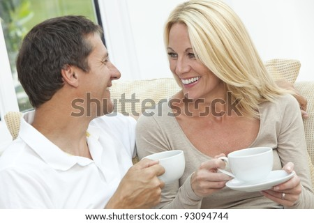 Attractive, successful and happy middle aged man and woman couple in their forties, sitting together at home on a sofa enjoying a cup or mug of tea or coffee