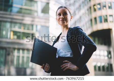 Attractive successful businesswoman dressed in stylish black suit holding folder in hand and looking away standing outdoors in urban setting on street.Modern architecture on promotional background
