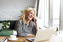 Attractive successful elderly businesswoman in striped blouse working in modern office, making phone call to potential client, having nice conversation, sitting at desk in front of open laptop