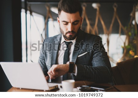 Attractive suited man checking the time on the watch while using laptop and drinking coffee in the coffee shop.
