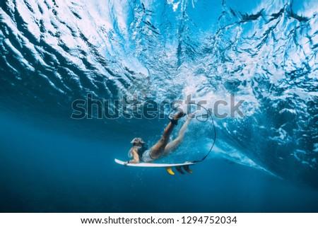 Attractive surfer woman dive underwater under wave.