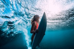 Attractive surfer woman dive underwater with under ocean wave.
