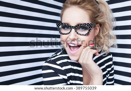 Attractive surprised young blonde woman wearing glasses on stripy background, beauty and fashion concept